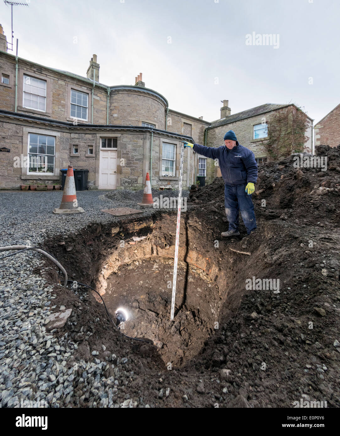 Builder inspects a hidden underground structure revealed by a void collapsing in a yard - Georgian brick icehouse, well or drain - Stock Image