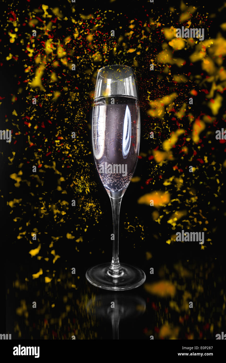 Flute of Champagne surrounded by confetti - Stock Image