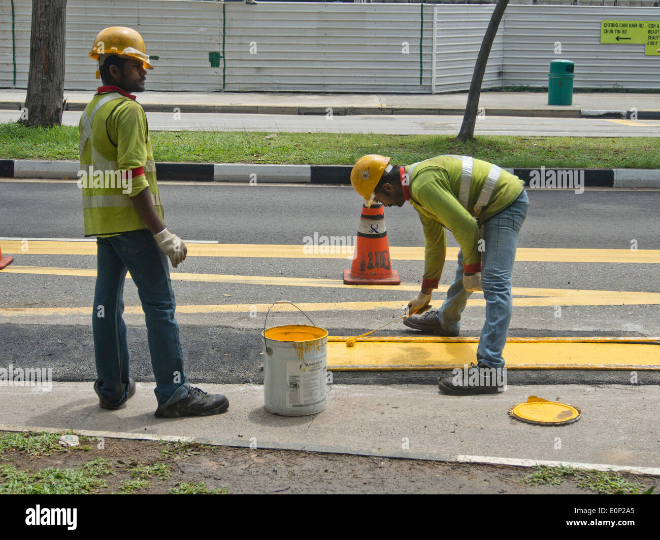 foreign migrant workers painting road signs in singapore