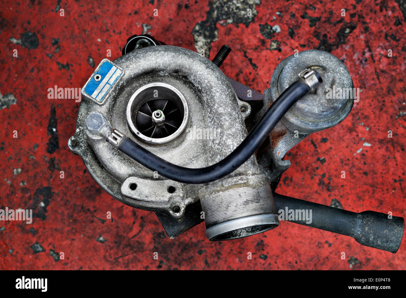 Old worn out turbocharger of a turbo diesel engine on a red background - Stock Image