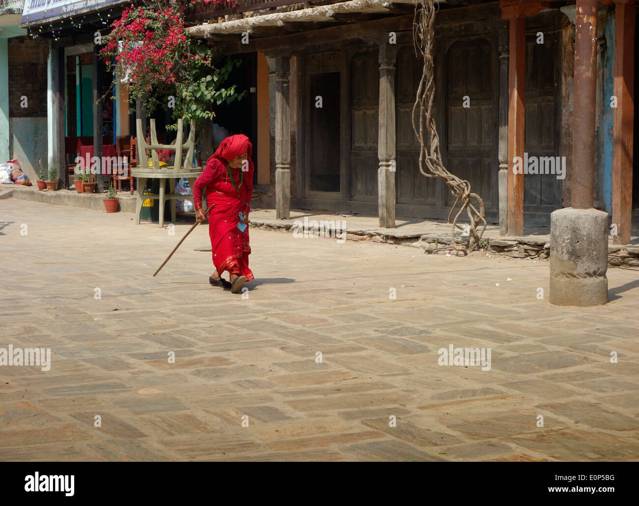 Old lady in red walking up town - Stock Image