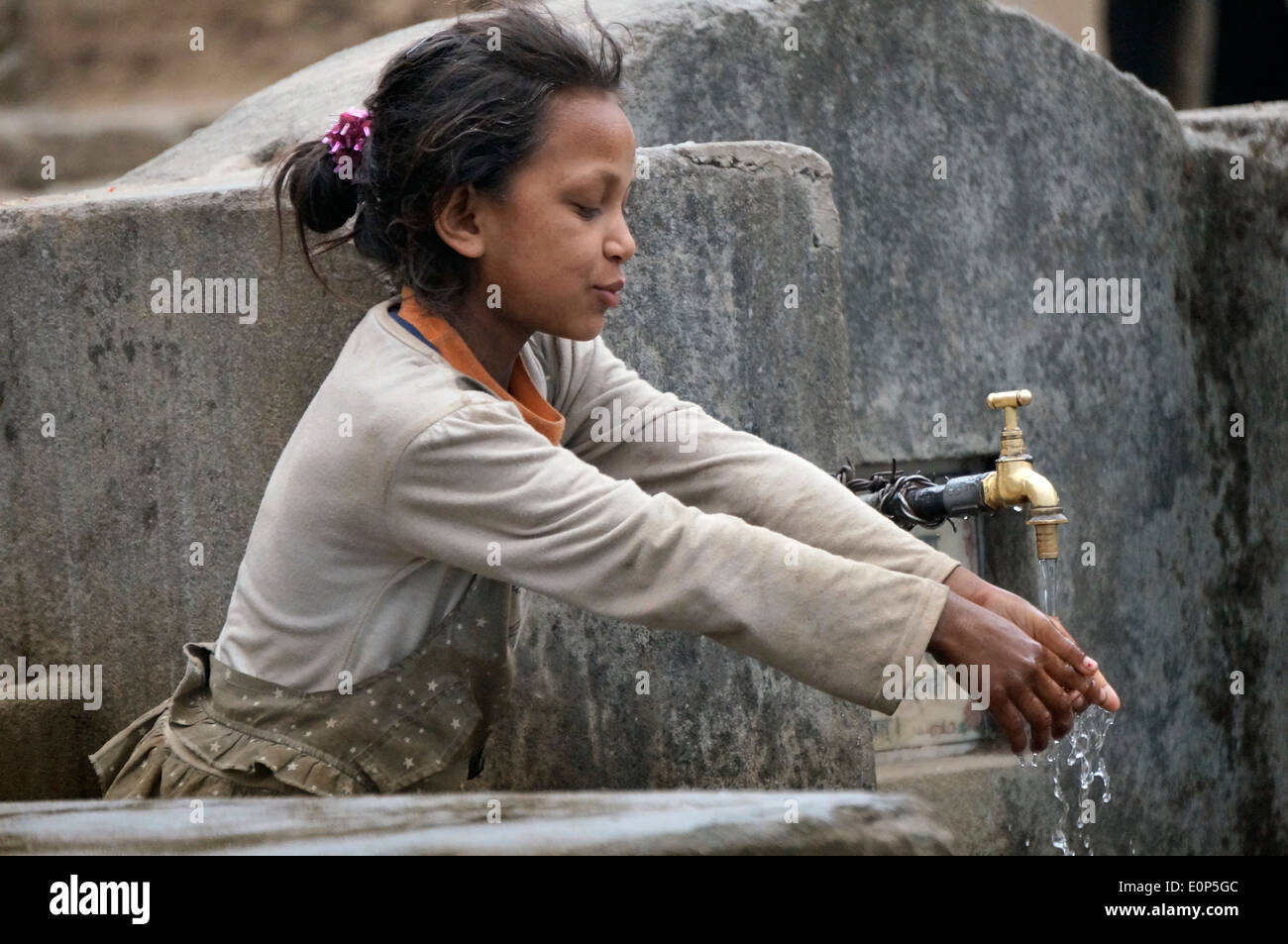 Young girl is washing hands at water faucet - Stock Image