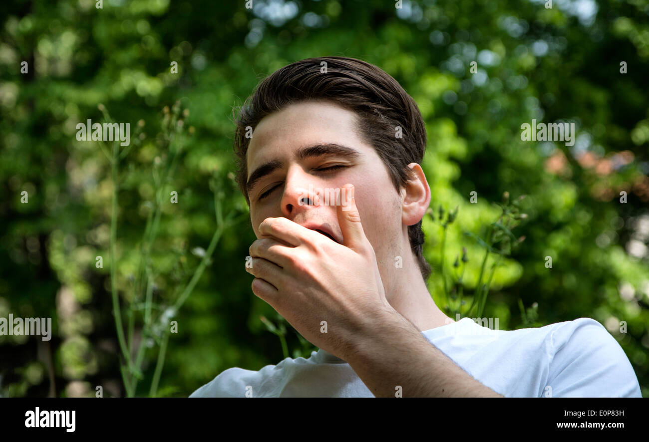 Bored or tired young man in a park yawning, covering mouth with his hand - Stock Image