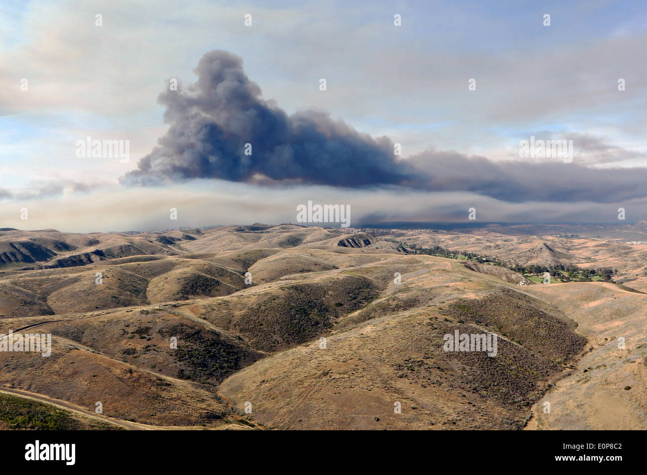 Smoke rises over the drought stricken foothills as the Tomahawk wildfire continues to burn May 16, 2014 around Camp Pendleton, California.  Evacuations forced more than 13,000 people from their homes as the fire burned across San Diego County. - Stock Image