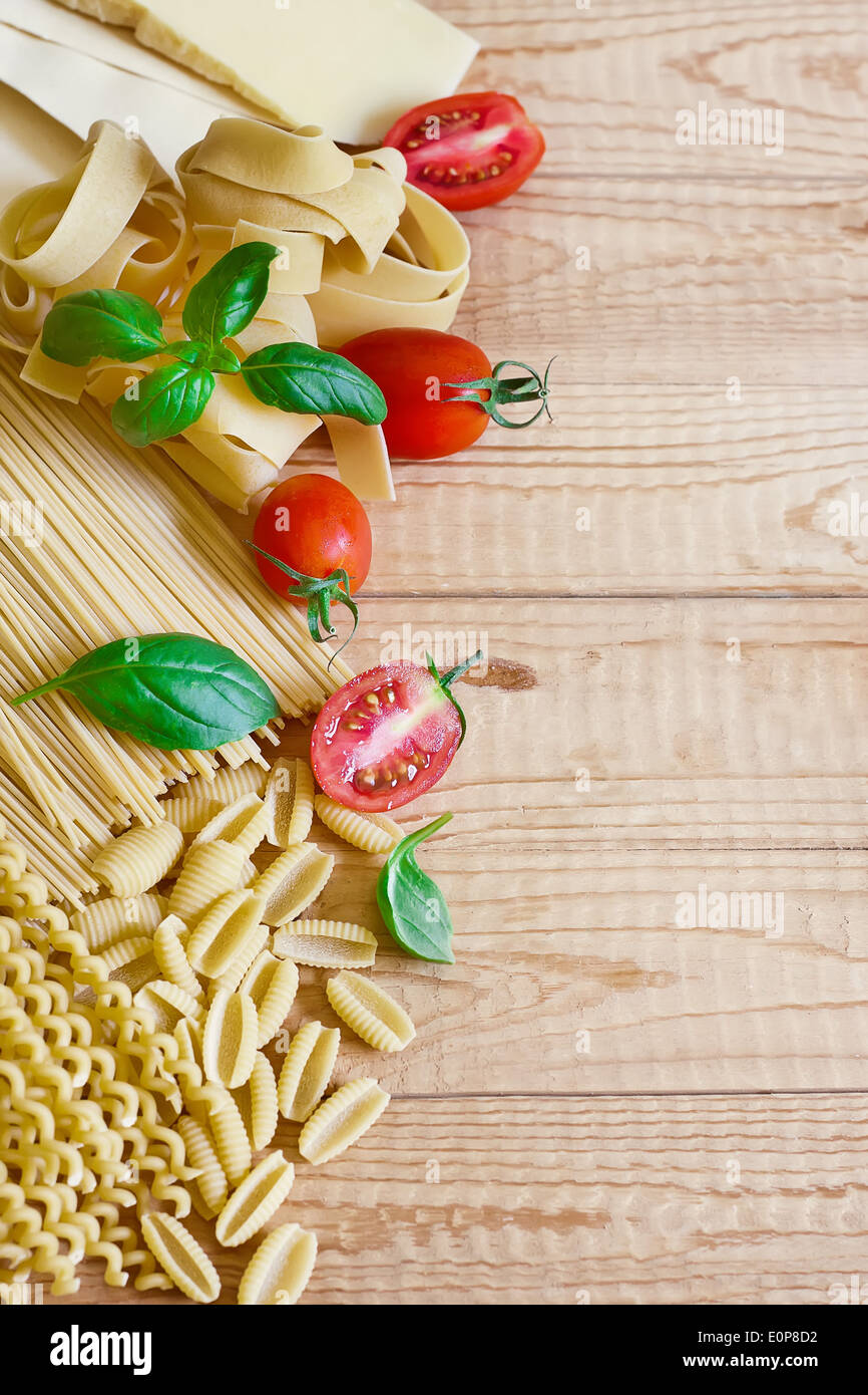 Mix of pasta, tomato, basil and parmigiano. Copy space background. - Stock Image
