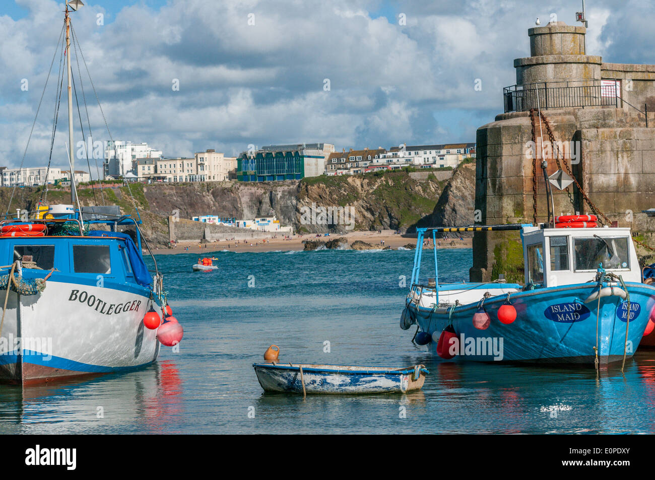 Two fishing boats and a rowing boat moored in Newquay harbour on a summers day. - Stock Image