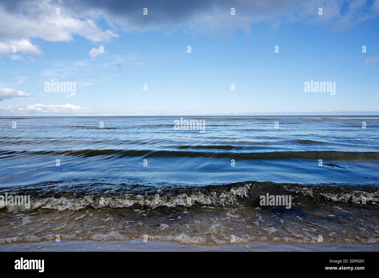 Ocean waves and very blue sky with some stormy clouds. Stock Photo