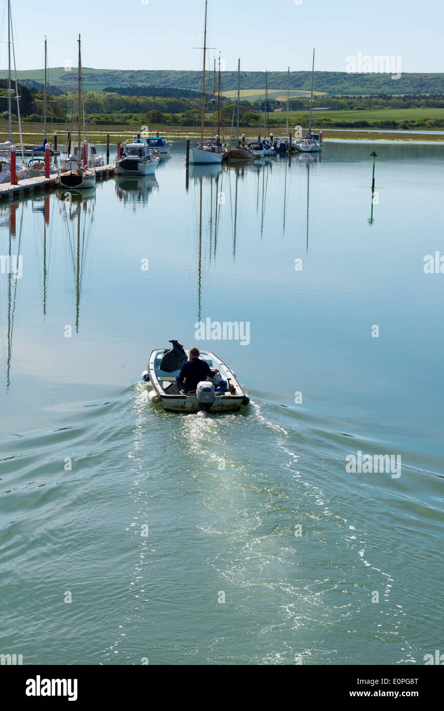 Coastal image showing a motorised boat moving through yarmouth harbour on the isle of wight in the uk Stock Photo