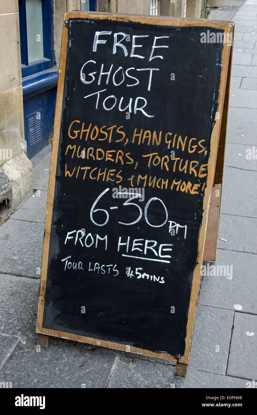 An A-board advertising a free ghost tour in Edinburgh's Old Town. - Stock Image