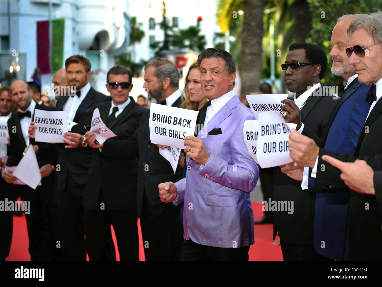 """(140518) -- CANNES, May 18, 2014 (Xinhua) --  Cast of """"The Expendables 3"""", holding up banners reading """"Bring back Stock Photo"""