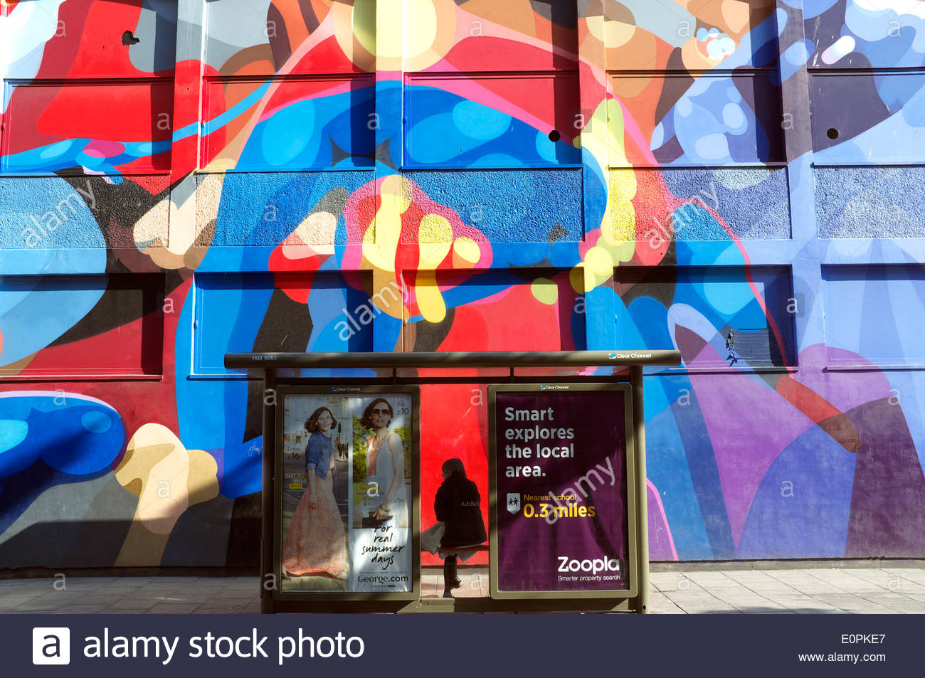 A lone passenger awaits at a bus stop in Nelson Street, home of many large scale street artworks. Bristol, UK. - Stock Image