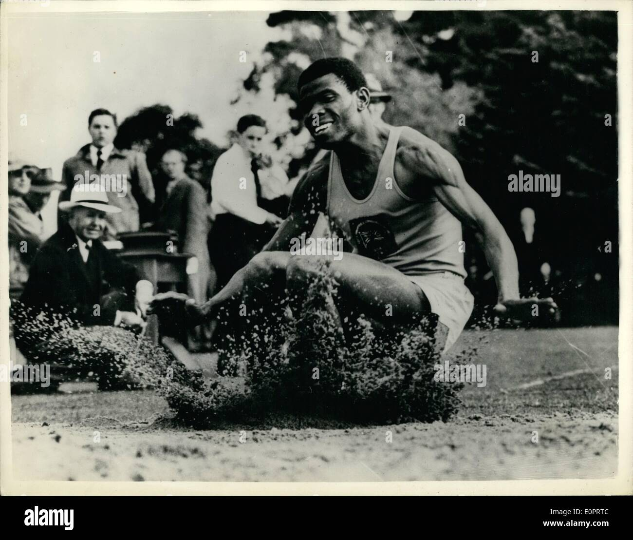 Nov. 11, 1956 - The Happy Athlete from Nigeria. Peter Esirt jumps over Seven Metres - at Melbourne: In a very happy mood is Nigerian Long Jumper Peter Esiri - landing during training at Melbourne for the Olympic Games. Peter jumps over Seven Metres - with ease. - Stock Image