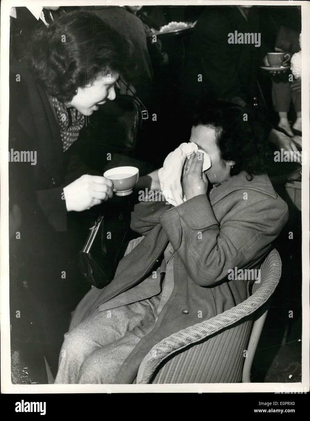 Nov. 11, 1956 - Hungarian refugees arrive in England. A tearful woman.: A party of 61 Hungarian Refugees arrived at Blackbushe Airport this morning. They are the advance guard of the 2,500 that this country is taking. Photo shows a tearful woman is offered a cup of tea on her arrival at Blackbushe airport this afternoon. - Stock Image