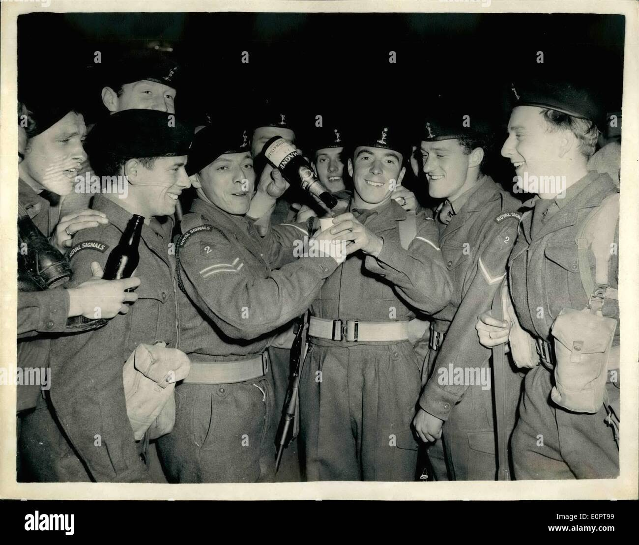 Dec. 12, 1956 - TROOPS FROM SUEZ ARRIVE IN LONDON COULD BE CHAMPAGNE-BUT IT ISN'T. Troops on leave from Port Said-arrived at Waterloo Station this afternoon. KEYSTONE PHOTO SHOWS: A happy party of members of the Royal Corps of Signals - at Waterloo this afternoon enjoy a drink - which should be champagne but which is really tea-- In centre (left) is CPL. J. GEORGESON of Liverpool and (right) L/CPL. London Airport KEACH of Bradford. - Stock Image
