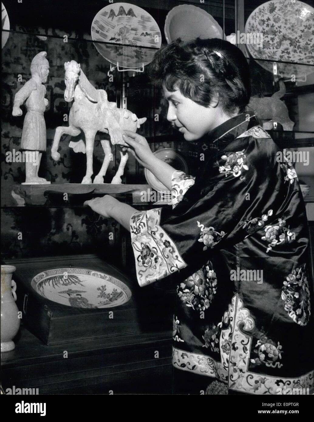 Dec. 12, 1956 - Nice customs in the ancient China: When in ancient times a Chinese presented a horse as a gift to someone he had to give also a man with the horse, who had to take care of the horse. The custom was used in the years about 618 after the birth of Christ. The man who had to take care of the horse was called Mafu. Such told us the young lady in the Kimono at the German Art and Antiquities exhibition just being held at the Haus der Kunst in Munich. On the picture you see a plastic from the time of the T'ang dynasty about 618 - 960 after Christ's birth, called ''Horse with Mafu. - Stock Image