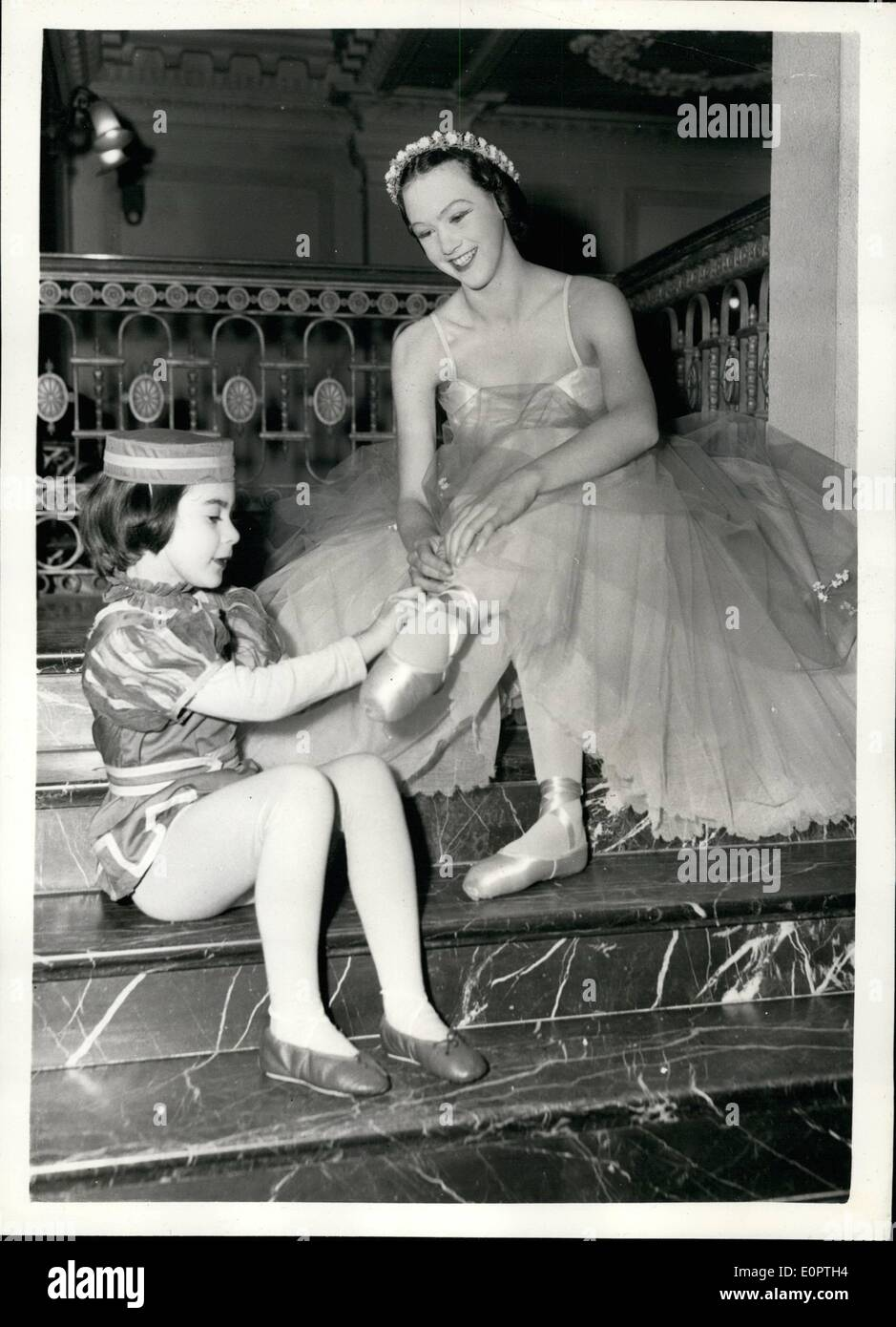 Dec. 12, 1956 - Children rehearse for ''Airs and Graces'' show. Niece of the Prime Minister takes part.: Children of many well known Dancing Schools were to be seen at the Scala Theatre this afternoon reahearsing for the annual 'Airs and Graces' - show for the Forces help Society. Photo shows: Elfrida Eden a sixteen year old niece of the Prime Minister receives a spot of assistance with her ballet shoes from Annabelle Gregory (6) before the rehearsal this afternoon. - Stock Image