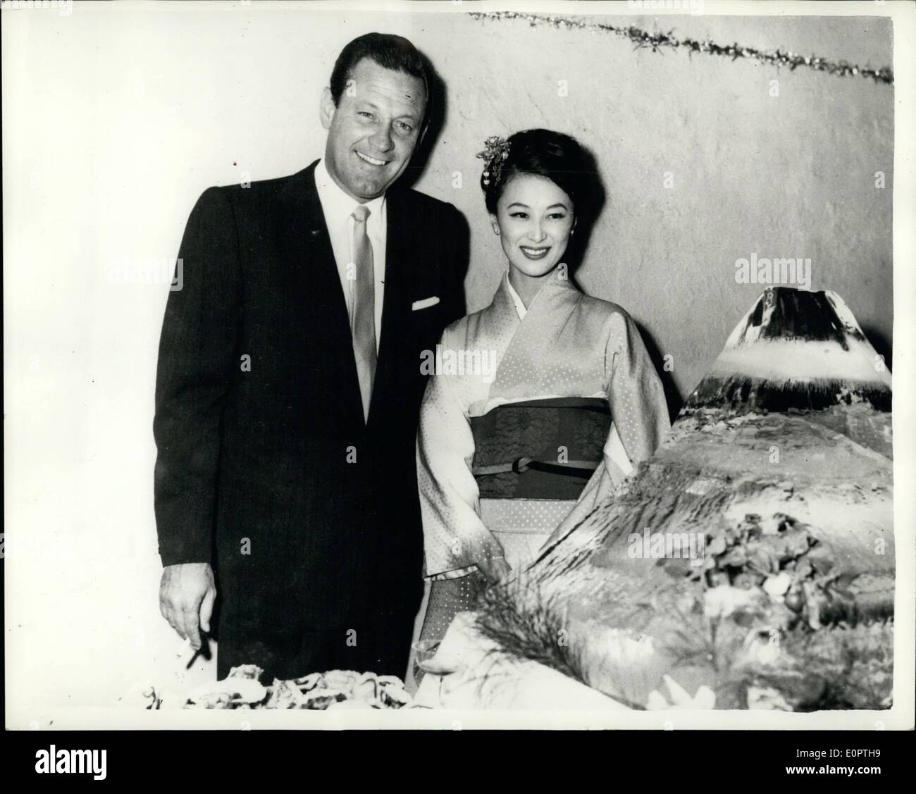 Dec. 12, 1956 - William Holden Attends Reception in Tokyo. Hollywood film star, William Holden attended a reception given in his honour at the Foreign Correspondents Club in Tokyo recently. He was enroute to Colombo, Ceylon, to play a major role in Columbia Films ''The Bridge on the River Kwai'', which will be filmed entirely in Ceylon. He is seen here with the lovely Japanese film star Keiko Kishi, who was the winner of the best actress award at the Asian Film Festival in Singapore, for her performance in ''The Refugee'' - Stock Image