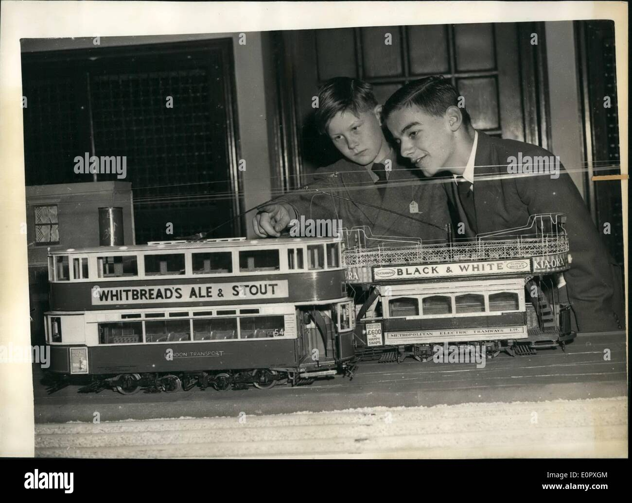 Apr. 04, 1957 - Opening of Model Railway Exhibition Ancient Trams.: Clive Ewen (10) of Crowthorn, Berks - and Reginald Davis (14) of Streatham - admiring models of (left) a London Transport Tram - and on right an ancient Metropolitan Electric Tram - at the Model Railway Exhibition which is being held at Central Hall, Westminster. - Stock Image