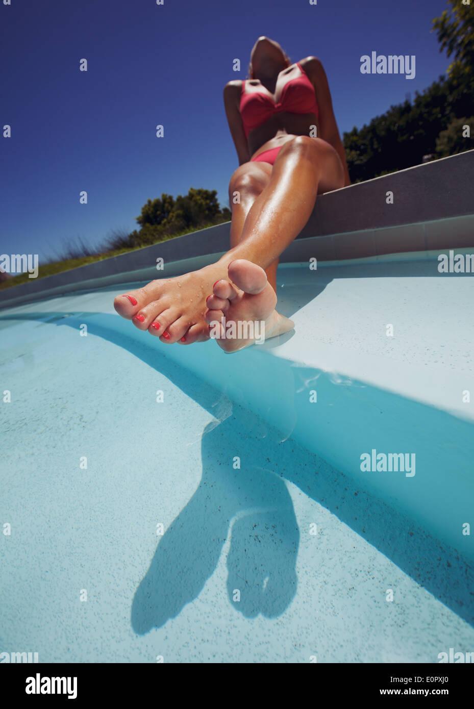 Low angle view of young woman wearing bikini enjoying the sun by the pool. Female model sunbathing by swimming pool. - Stock Image