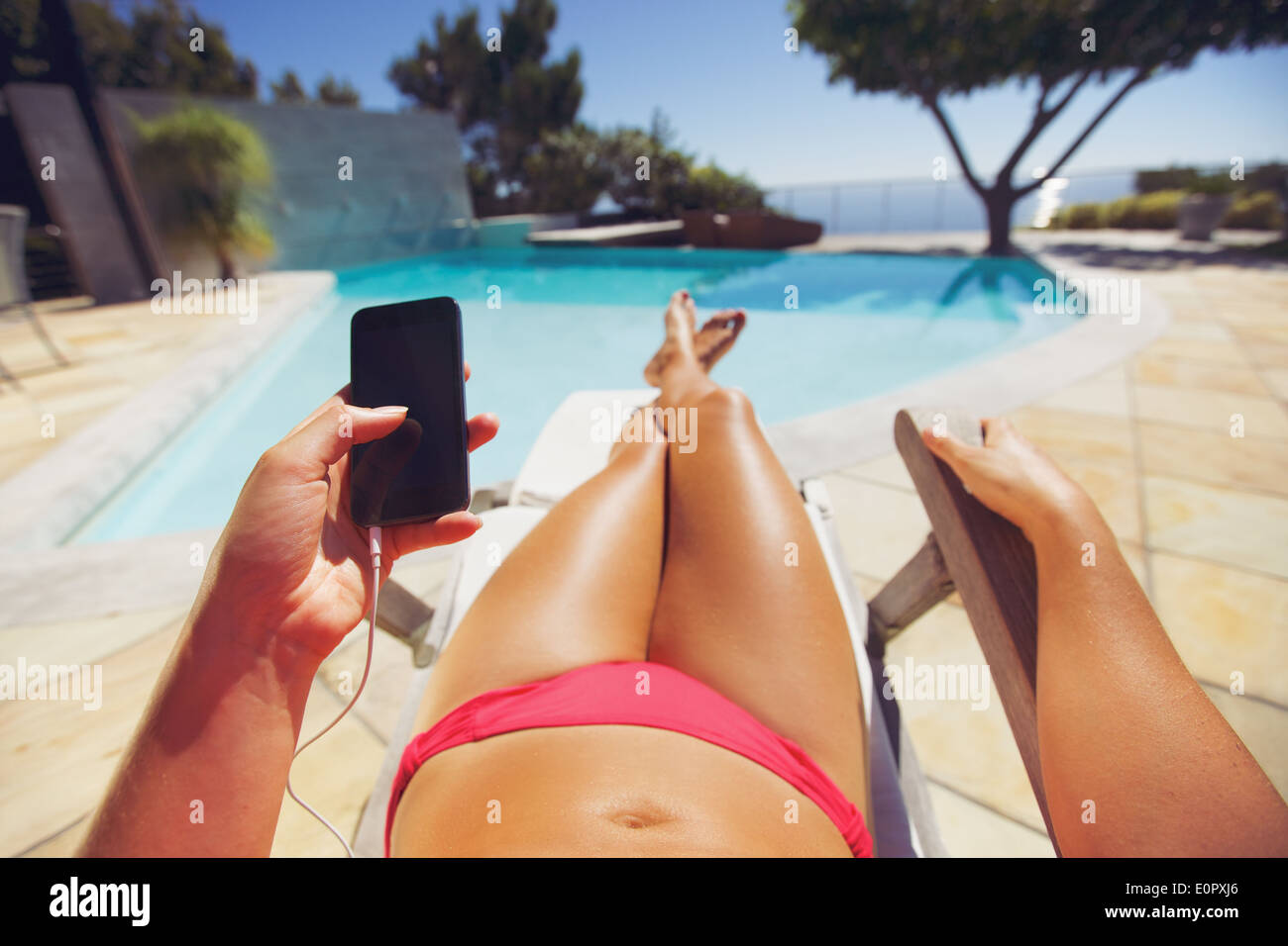 Young woman holding a smart phone by the pool. Female model relaxing on a deckchair using mobile phone. - Stock Image
