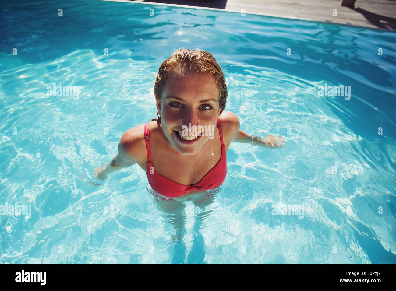 Overhead view of beautiful young lady wearing red swimwear standing in a pool looking at camera. Pretty young woman relaxing - Stock Image