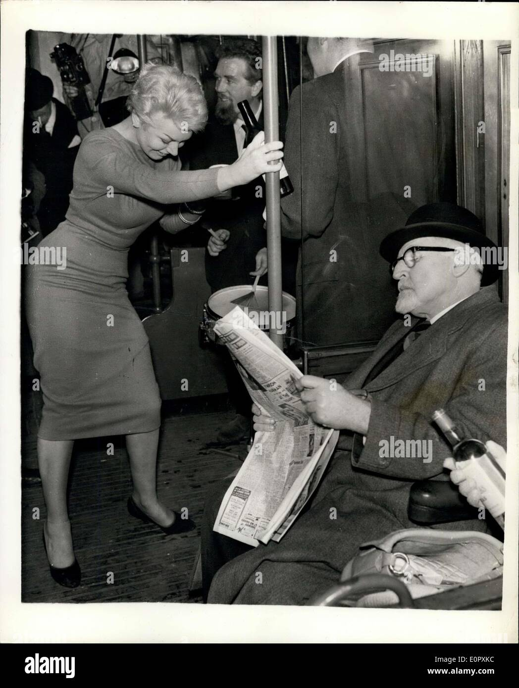 Apr. 12, 1957 - The Queen's Cousin Goes Rockin' At A Fantastic Party On An Underground Train The smart set went Underground last night and rocked non-stop around the Inner Circle route from Charing Cross to Charing Cross. They skiffled and rocked their way through Euston, Kings Cross, Farringdon, and Edgware-road, and the price of the round tour was two shillings. That's what each of the 75 guests - including the Queen's cousin, the Hon. Gerald Lascelles, paid for their tickets - Stock Image