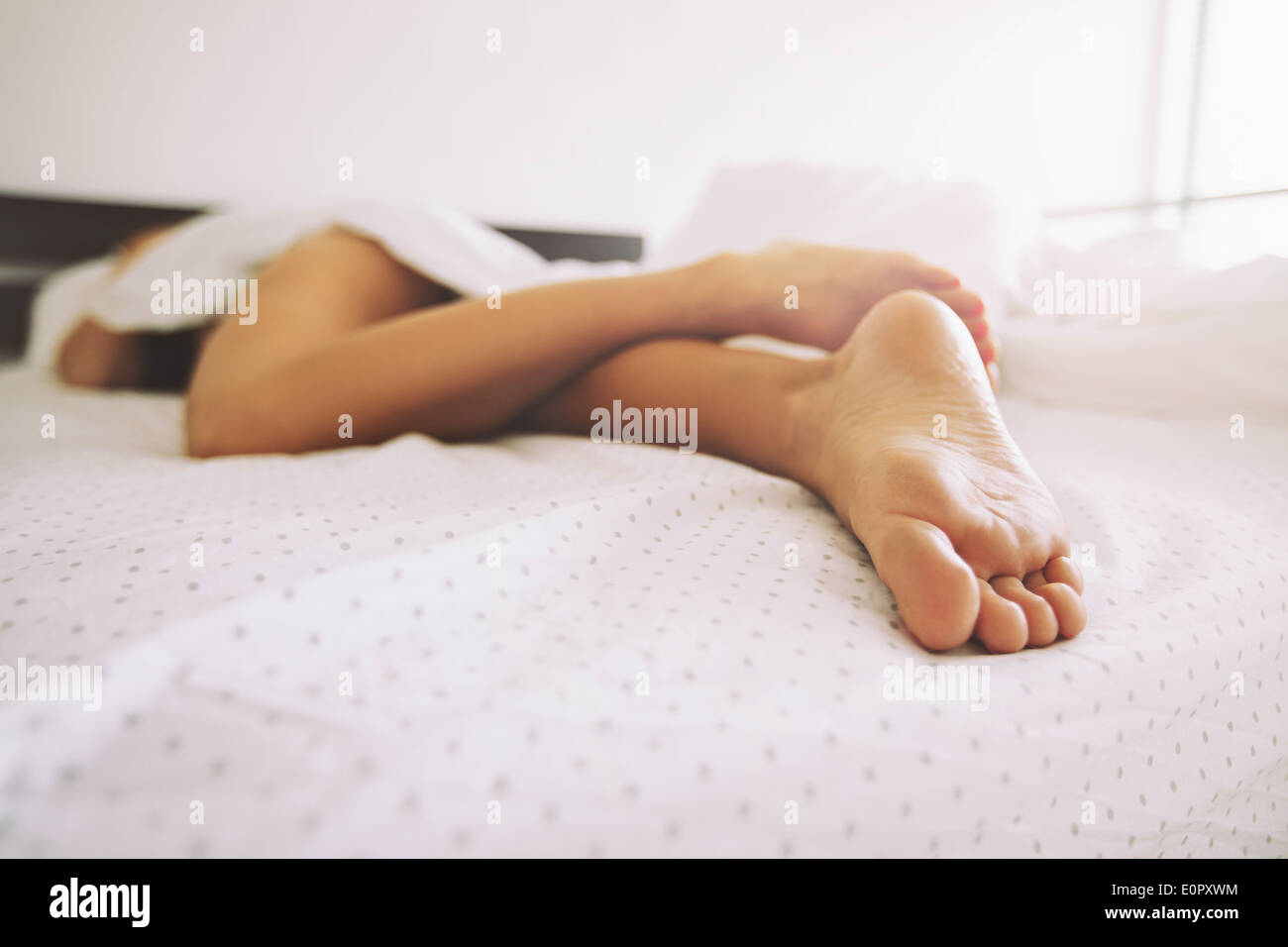 Young female sleeping in bed at home with focus on legs. Feet of woman lying on bed. - Stock Image