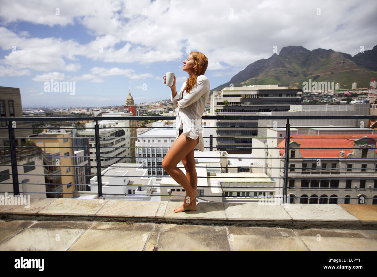 Beautiful young woman wearing a shirt only standing on balcony having cup of coffee, enjoying sun on a hot summer day. - Stock Image