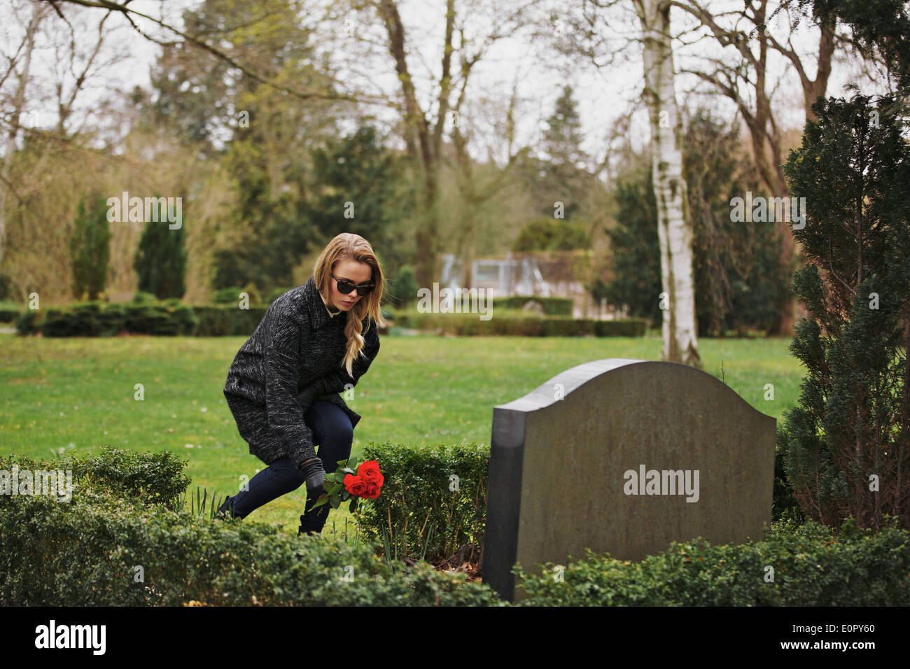 Young woman placing flowers on the grave of a deceased family member at cemetery. Young lady at the cemetery paying respects. - Stock Image