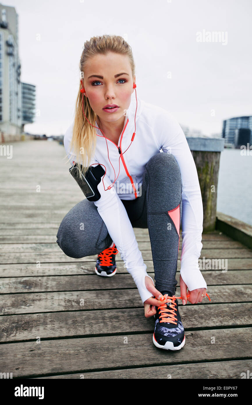 Pretty young woman tying her shoelaces before a run. Fit young female runner training outdoors. - Stock Image