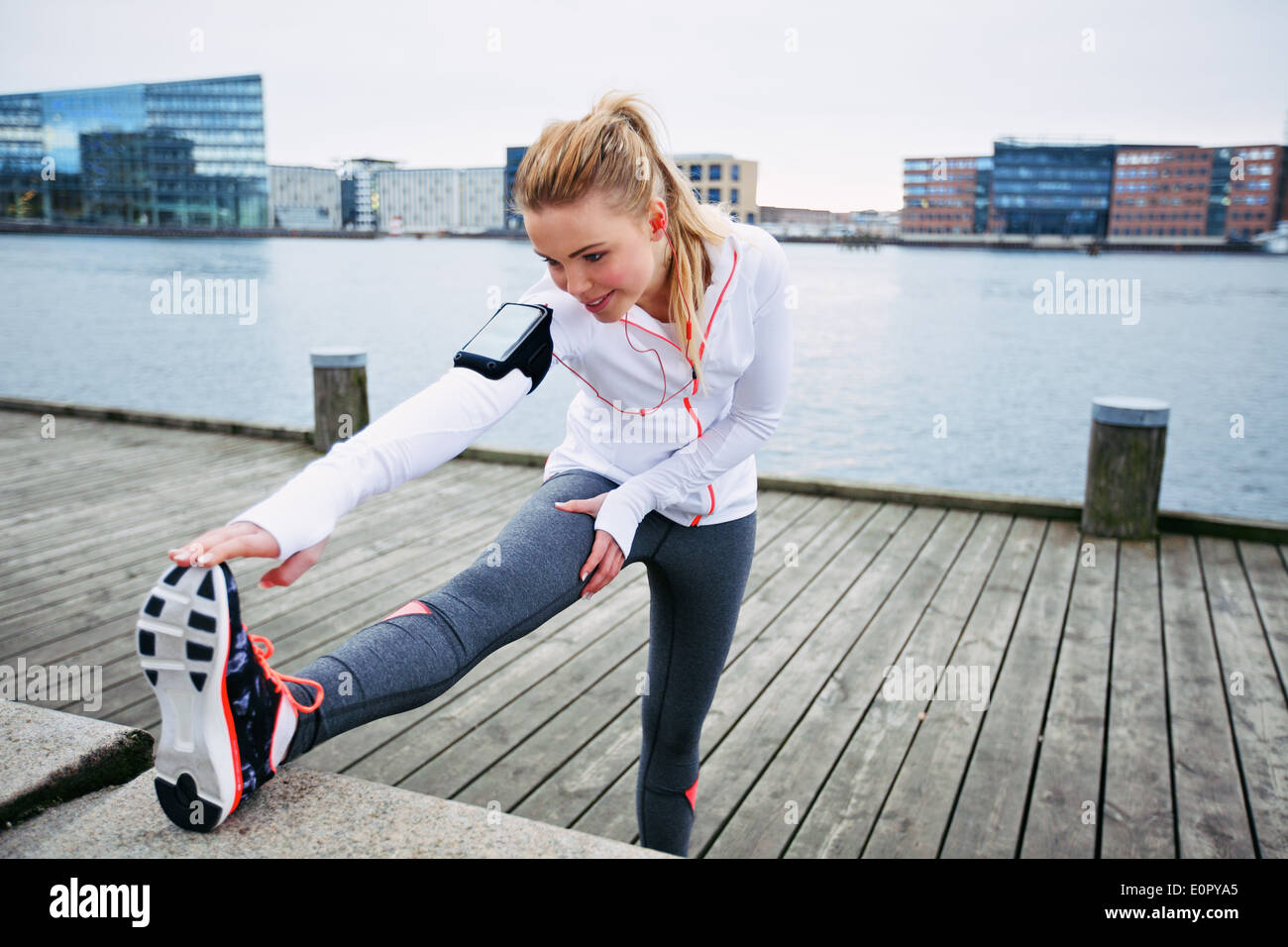 Fit young woman stretching before a run. Young female runner stretching her muscles before a training session - Stock Image