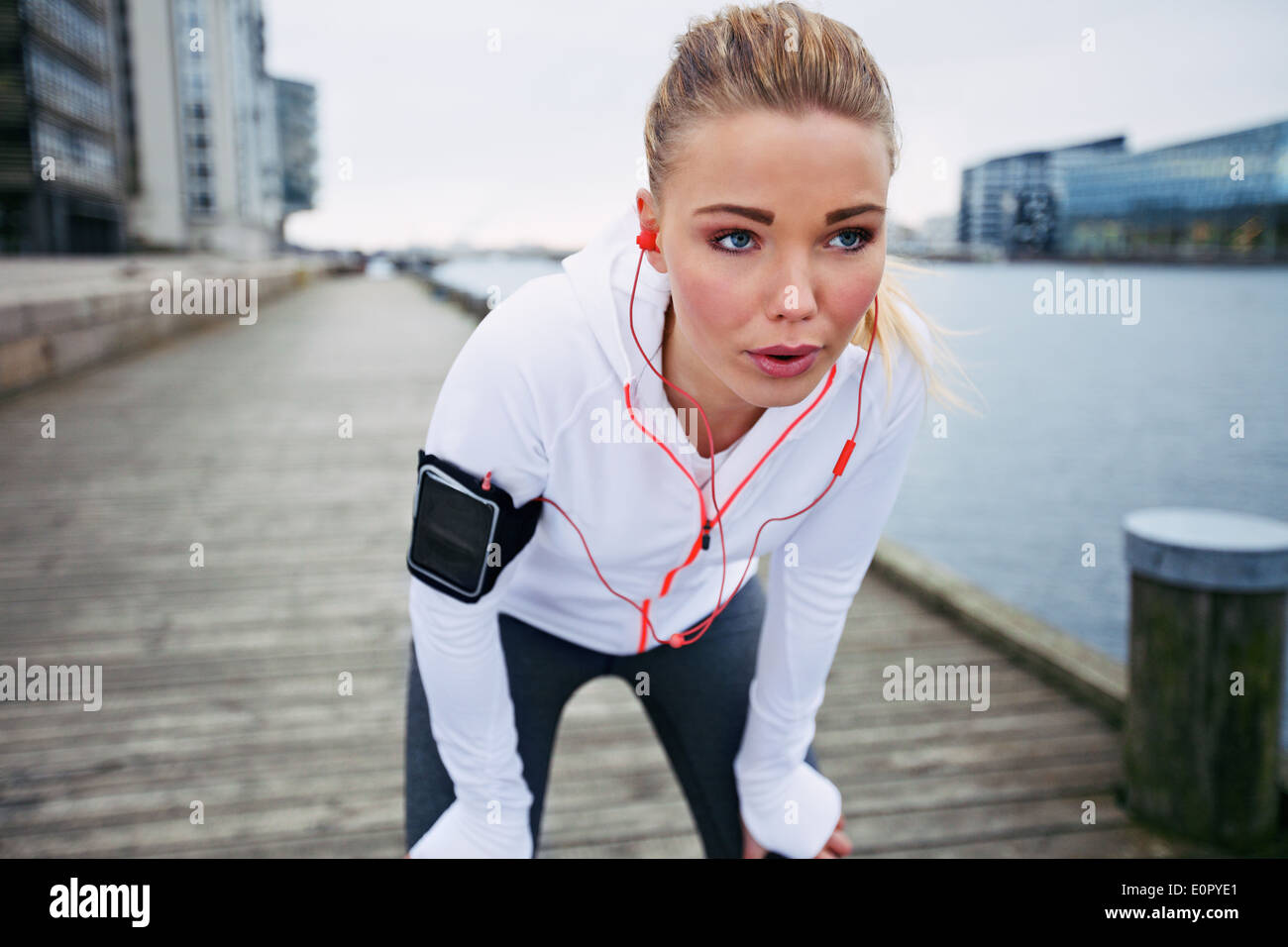 Young woman taking a break from exercise outdoors. Fit young female athlete stopping for rest while jogging along the river. - Stock Image