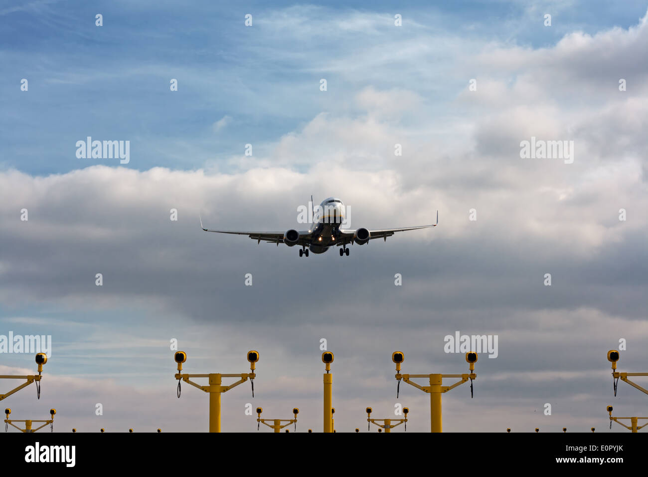 Passenger plane on final approach, with landing lights in view - Stock Image