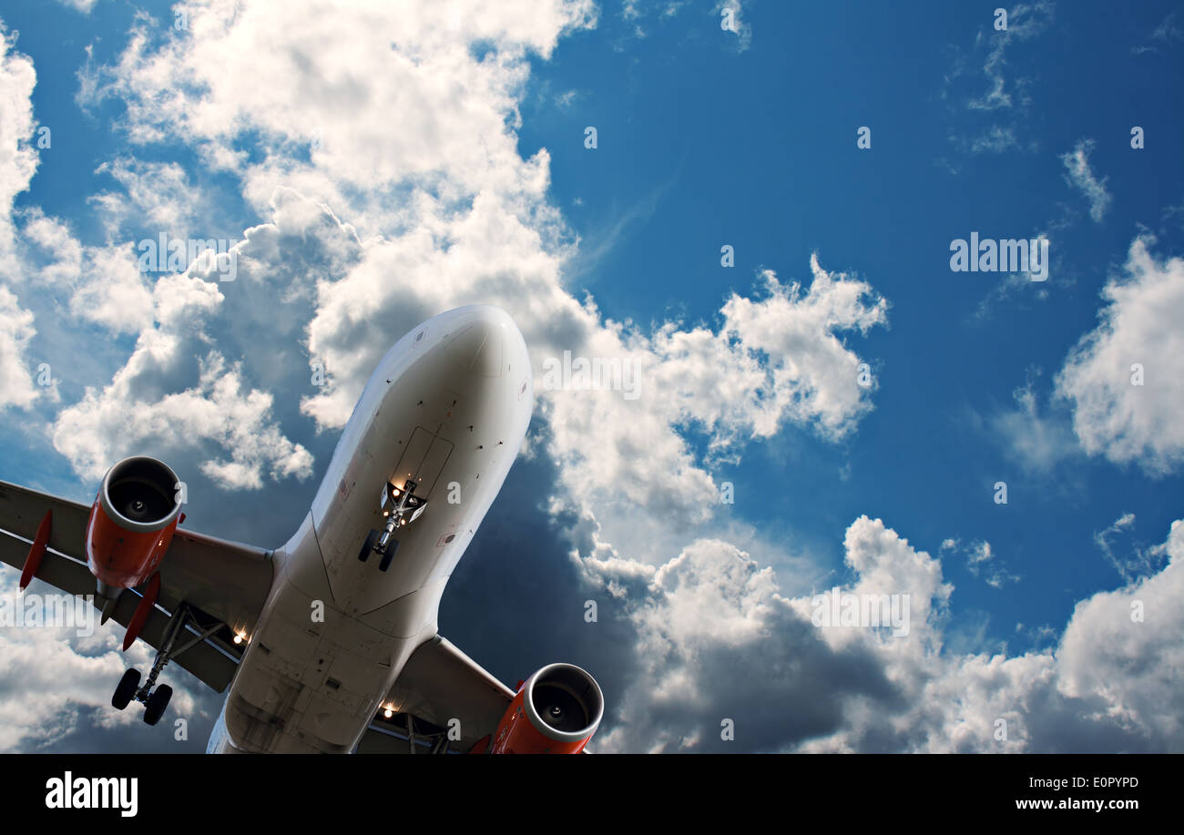 Passenger jet against a blue sky with white fluffy clouds - Stock Image