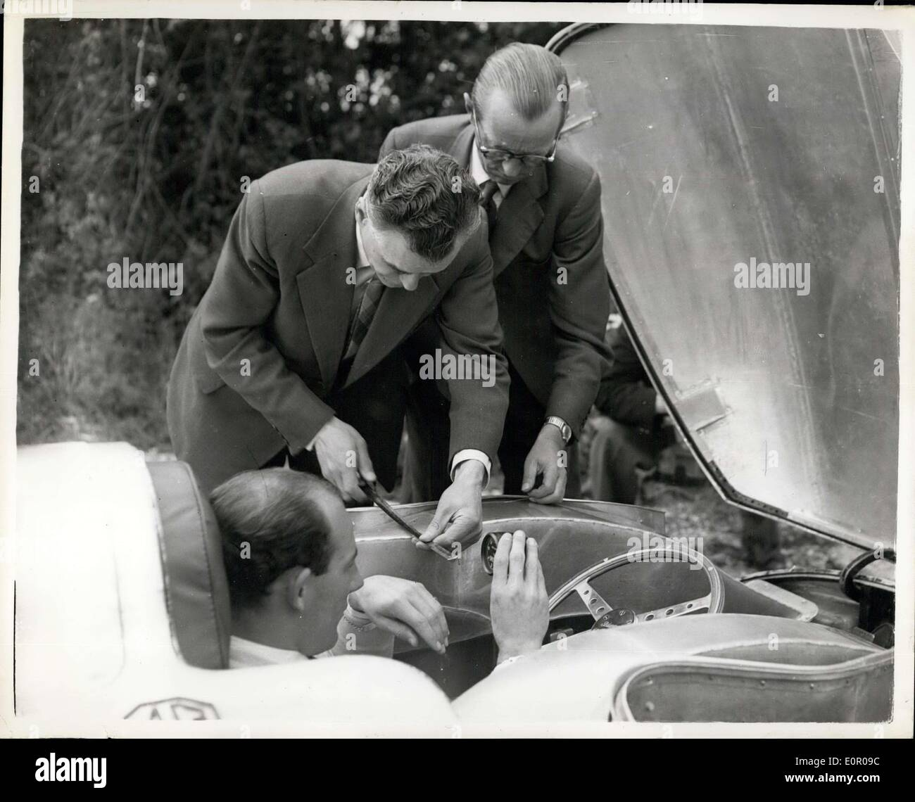 May 30, 1957 - Stirling Moss to attempt a world speed record; An M.G. car has been specially built for British racing driver, Stirling Moss in an attempt to beat the world land speed record for 1,500 c,c, cars at Salt Flats, Utah, USA in August. The present record for class of this class is 204.2 mph. which was set up in 1939 also in an MC. Photo Shows Stirling Moss, seen in the car which is tailor made yesterday. Holding the measure is Mr. Sidrey Enever, Chief Engineer and designer, and behind him is rm. John Thornley, (Director & General Manager o the MC Car CC) - Stock Image