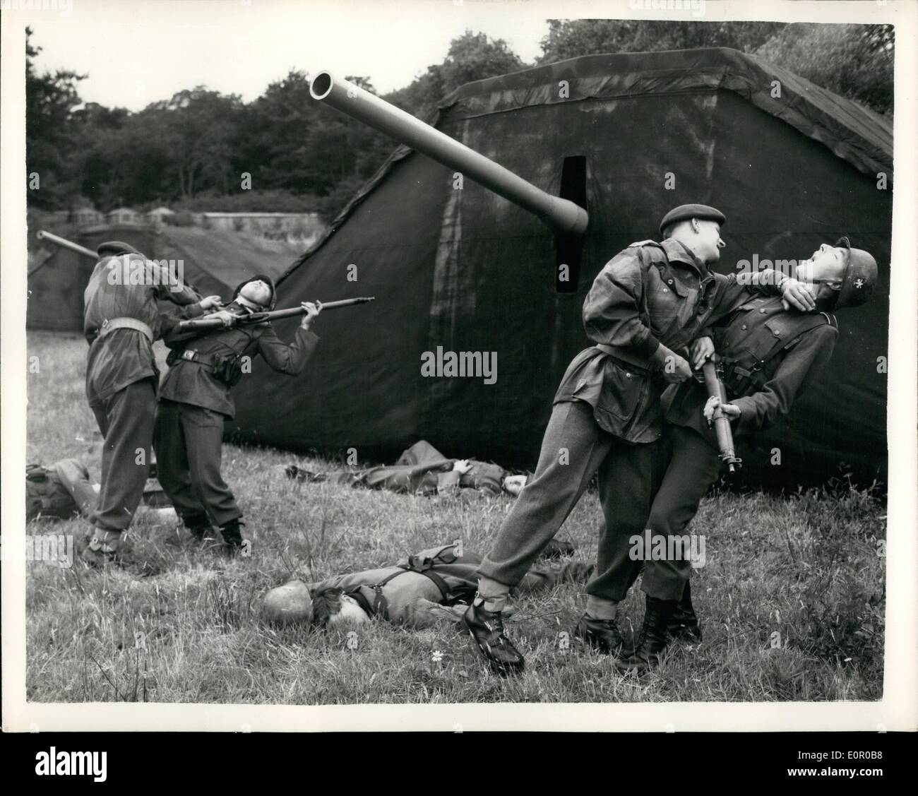 Jul. 07, 1957 - Rehearsing battle scene for searchlight tattoo.: A rehearsal was held at Aldershot this morning of the battle scene of the White city searchlight tattoo. The scene shows the silencing of the Merville Battery by the coast of France on D-Day. Men in german uniforms took the part of the enemy. Photo shows memebers of the Srd. Battalion parachute right after having made a ''Parachut landing'' attack a German gun strongpoint during the rehearsal thi morning. - Stock Image