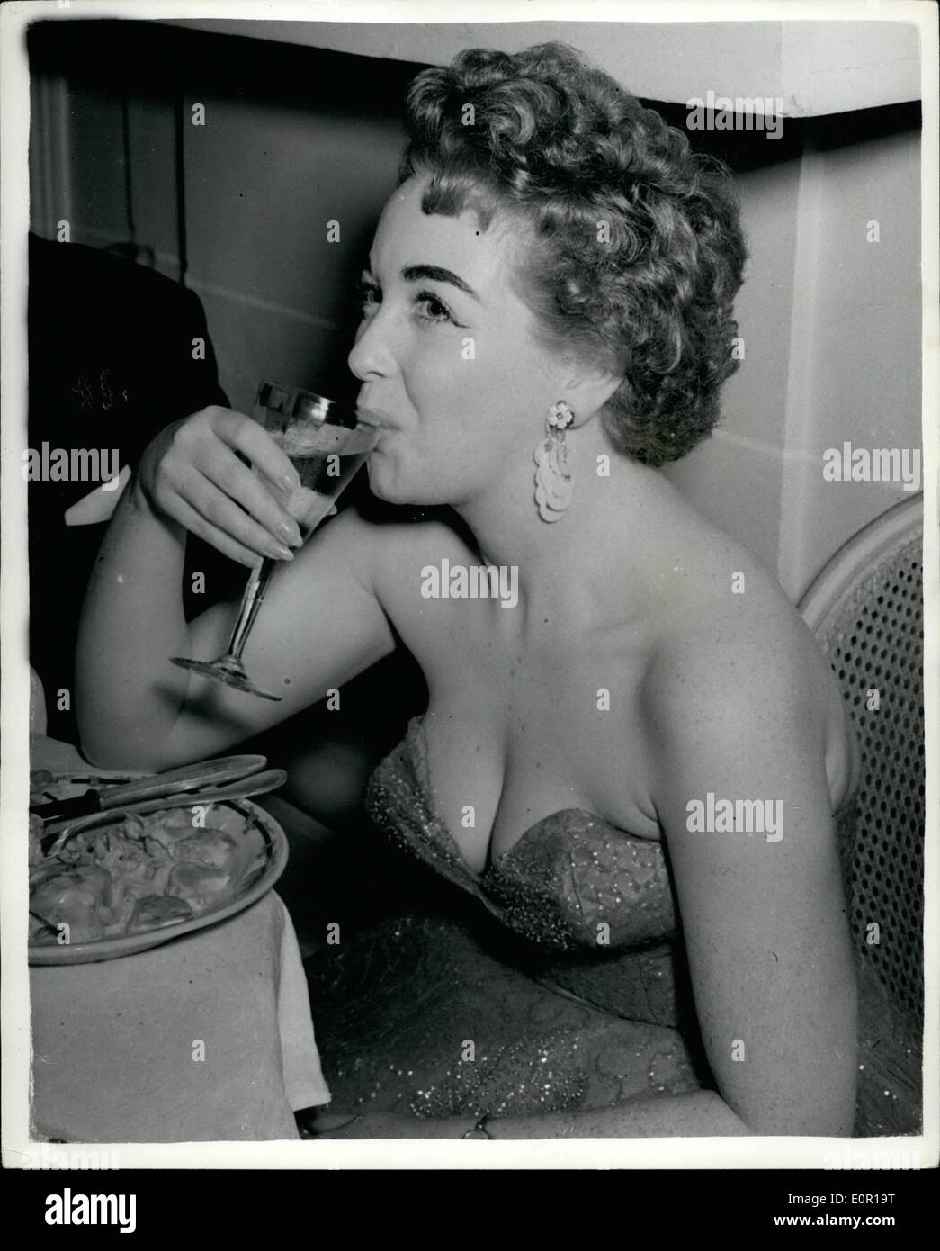 Aug. 08, 1957 - Socialites attend £20,000 Charity Party at Deauville. Singer takes a drink. More the 900 guests attended the Ball of the Little White Beds at £15, a time held on Saturday at the Deauville Casino. The wealthy guests struggled to eat their 9 course dinner in the overcrowded dining room usually accommodating 350. Gowns were torn but £20,000 was raised for charity. Keystone Photo Shows: Marion Ryan from Leeds, a singer in Ray Ellington's band, takes a drink when she attended the Charity ball. JSS/Keystone - Stock Image