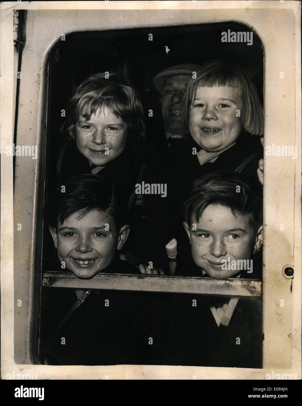 Mar. 03, 1958 - Sponsored Families emigrate to Australia. Four youngsters from stoke newingto: Sixty two families sponsored by the Rotary Organisation in Australia - left Waterloo Station this morning for the liner Orsova on way to a new life in Australia. Photo shows Four youngsters of the Stewart family of Stoke Newington - in the window of their carriage at Waterloo. They are Top L-R:- Susa: ( 4) ; Angela ( 5) ; with bottom L-R:- Malco ( 7) and Ian ( 8 ). They are going to Tasmania with their parents Mr. and Mrs. C.B.J. Stewart. - Stock Image