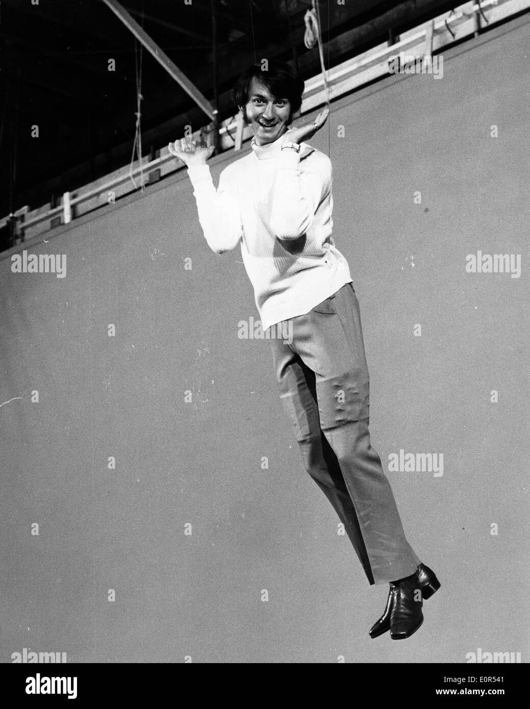 Singer Mike Nesmith swinging in a scene from a new Monkees' film - Stock Image