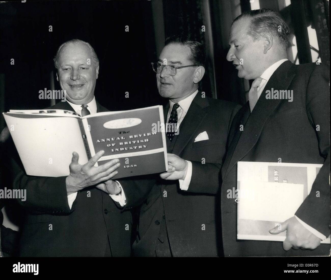 Apr. 04, 1958 - Foreign Secretary hands copies of British Industry Review to American and Canadian officials - at house of Commons. Mr. Selwyn Lloyd the Foreign Secretary this afternoon presented copies of ''The Annual Review to British Industry 1958'' to the American Ambassador Mr. J. H Whitiney for transmission to Pres. Eisenhover - and to Mr. George Dw the Canadian High Commissioner for transmission to Mr.Diefenbaker. the ceremony was held in the members dining room in the house of Commons. The book is designed to boost British exports to the U.S. and Canada. Photo shows Mr - Stock Image