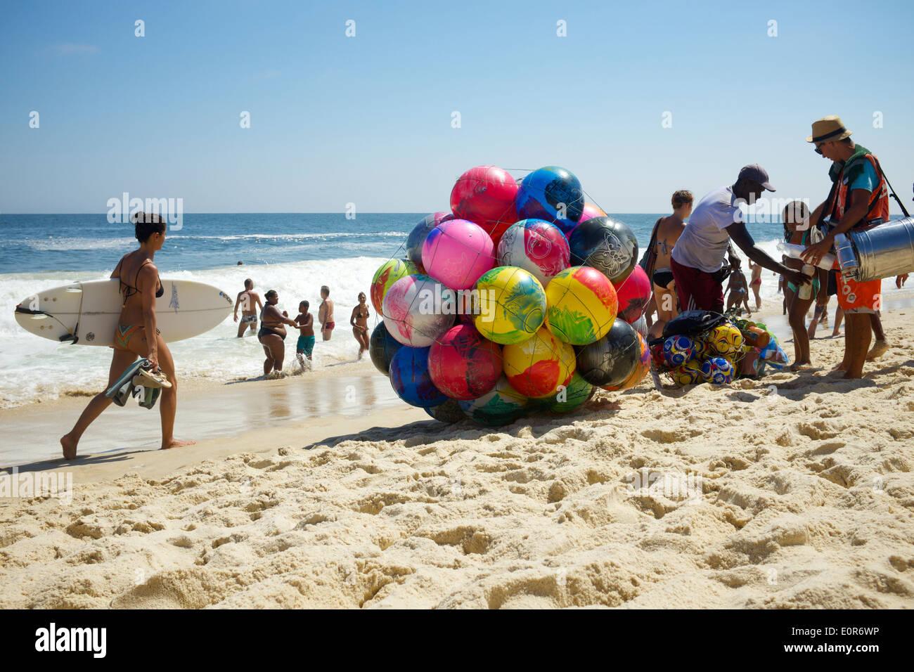 RIO DE JANEIRO, BRAZIL - JANUARY 20, 2014: Woman walks with surfboard on Ipanema Beach past vendors selling beach balls and food - Stock Image