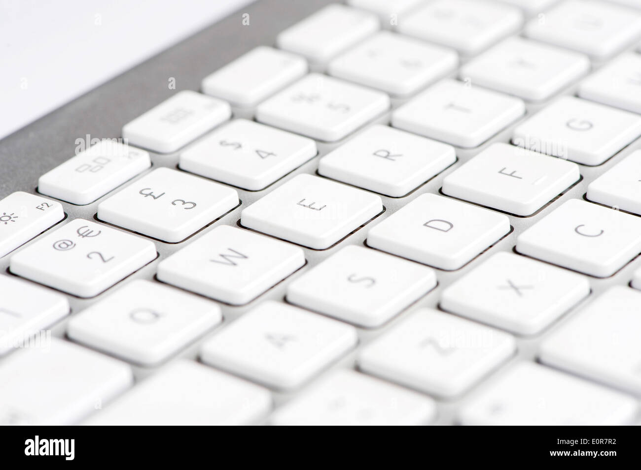 Apple mac white Keyboard focused on the letter E - Stock Image