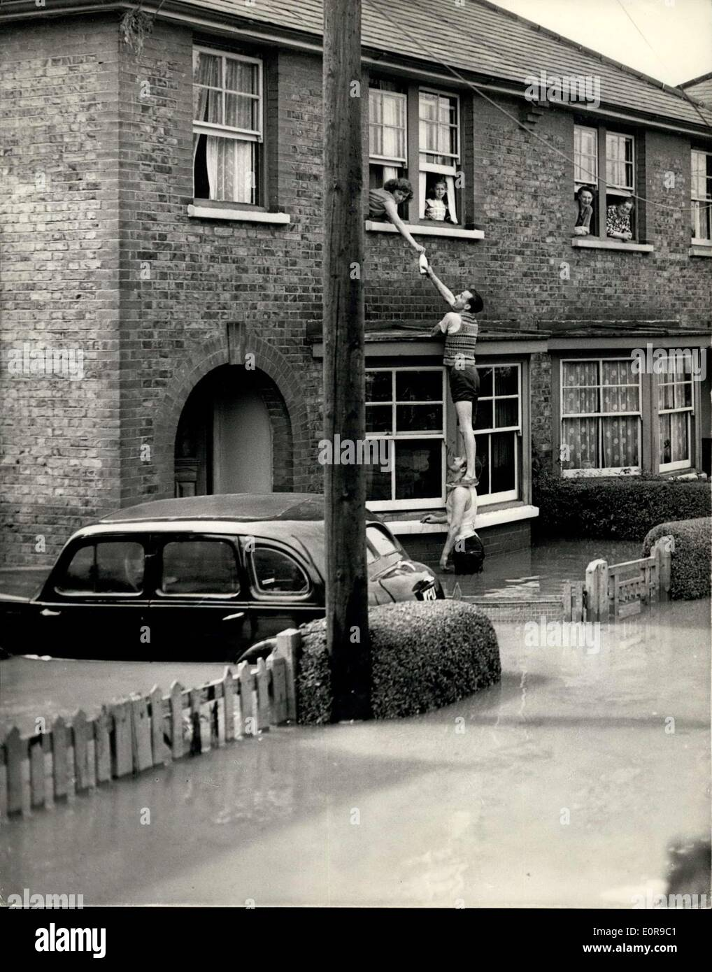 Sep. 06, 1958 - Flood scenes after last night's storm; Much damage was caused last night in what was described as ''one of the most spectacular electrical storms of the century'', which swept the South of England. Many houses were flooded and buildings damaged. Photo Shows A human chain was formed to deliver the milk to marooned householders, in flooded Wickford, Essex, today. - Stock Image
