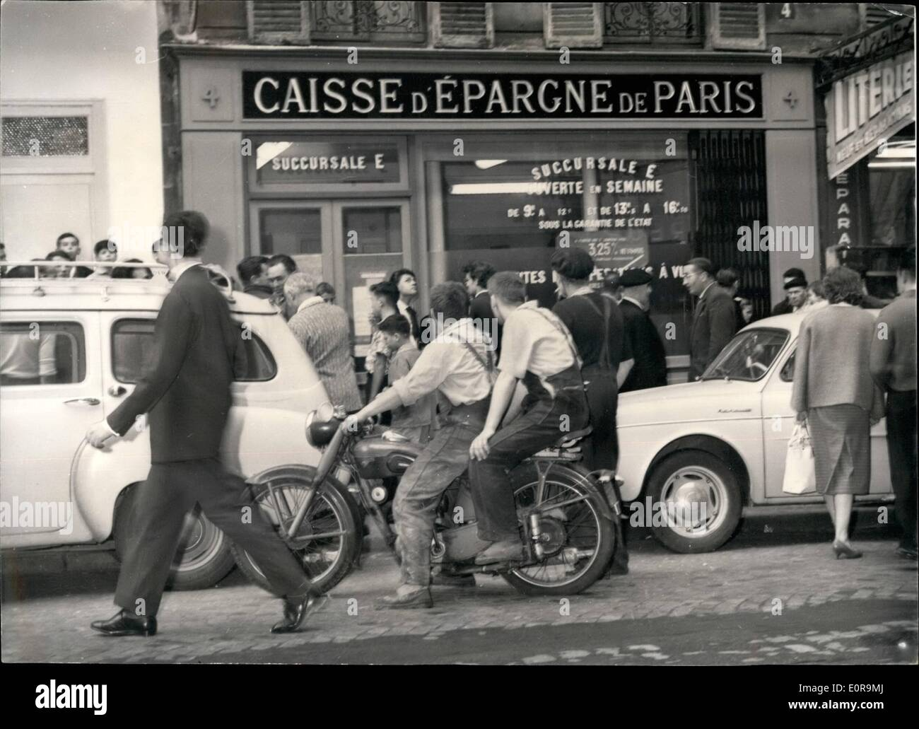 Sep. 09, 1958 - Daring Hold-Up In Broad Daylight: Paris Savings bank Robbed Of 2,500: Four men wearing dark glasses and Mackintoshes carried out a spectacular hold-up in a Paris saving banks, in the Rue Claude Bernard, not far from Sorbonne University this morning after locking up the bank teller and the rest of the staff in a room the grabbed 2,500 worth of bank notes and quietly left the bank before the staff had the time to call the police. Crowd before the bank after the robbery, - Stock Image