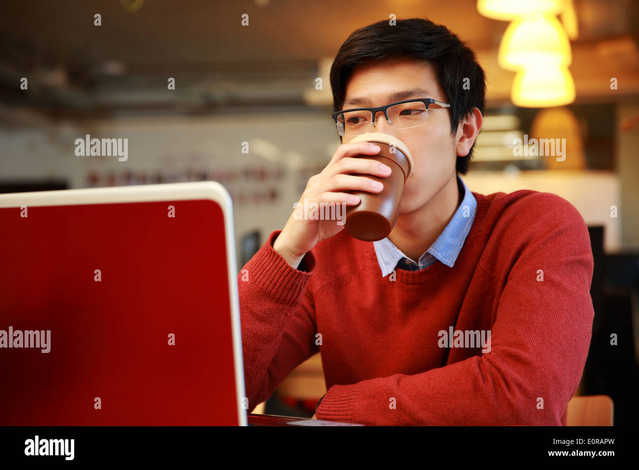 Young asian man working on laptop and drinking coffee - Stock Image