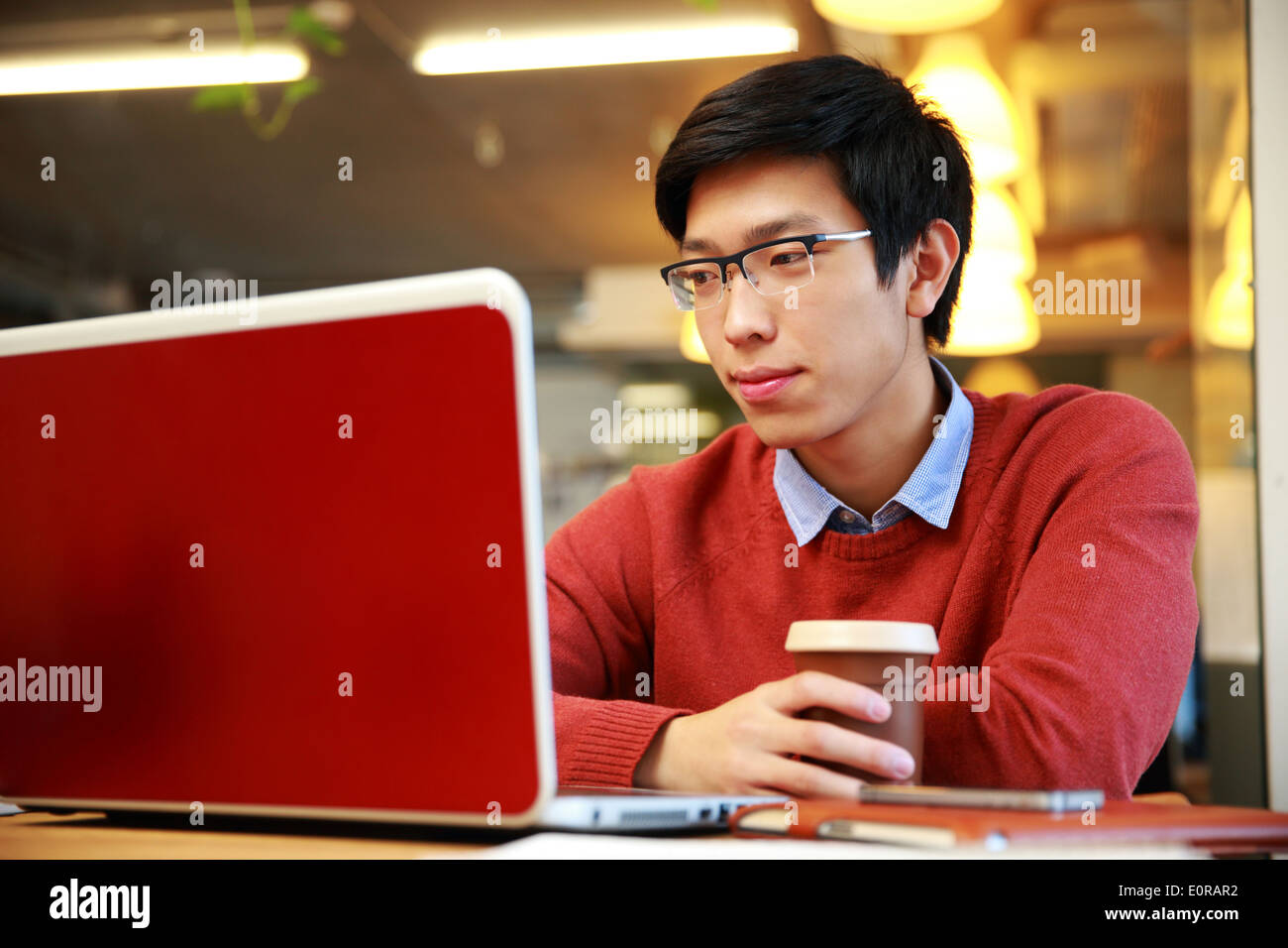 Young asian man in glasses working on laptop and holding cup of coffee - Stock Image