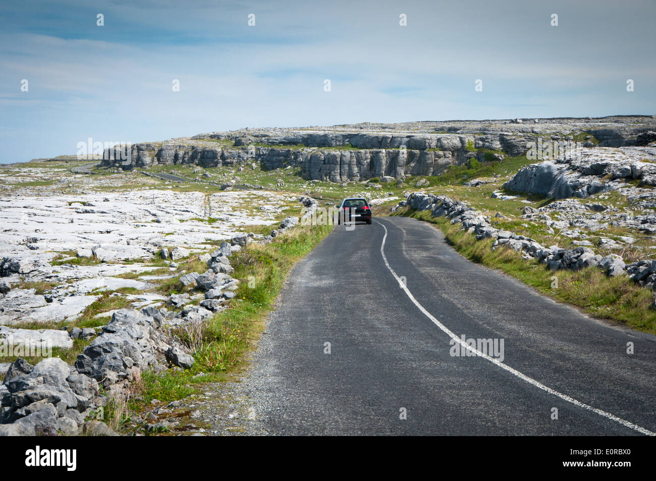 Car disappearing into the distance on the Touring Route through the Burren in County Clare along the Wild Atlantic Way on the West Coast of Ireland - Stock Image