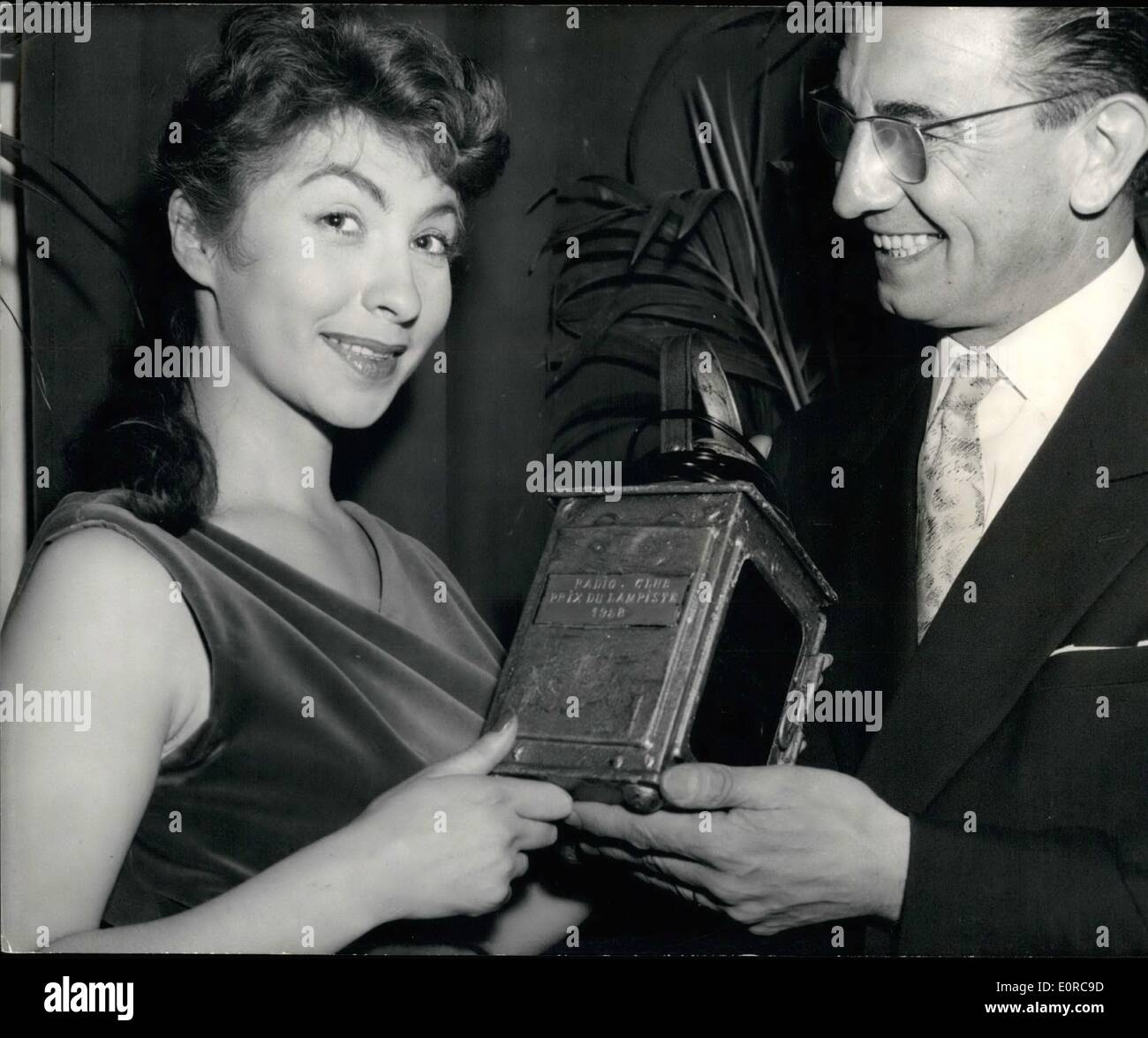 Dec. 12, 1958 - Railwaymen award prize to Belgian singer: Members of the Railwaymen's Radio Club awarded the ''Prix de Lampiste'' to a young Belgian singer Dora Neri today. ''Lampiste'' is the French for signal man, a word generally used  as a reference to an obscure person who always takes the blame when somethin wrong happens. The prize goes to reward an unknown singer of the talent. Photo shows M. Wiart, vice-chairman of the Radio Club, handing the prize to Dora Neri. - Stock Image