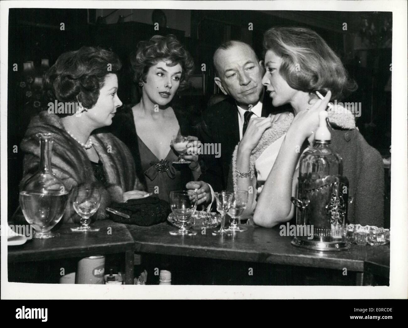 Jan. 01, 1959 - The lucky squire of London town Noel Coward escorts three fascinating women. Mr.Noel Coward was surely the luckiest man in London last night, when, beaming like a benevolent sultan he escorted three ofthe world's most fascinating women, Kay Kendall, Vivian Leigh and Lauren Bacall , to the St Martin's theatre. They went to see ''The Grass is Greener'' starring their mutual friend, Celia Johnson . The party had been laid on by Vivian Leigh. Photo shows During the interval Noel taken the trio for a drink and here he is chatting at the bar to (L.to R - Stock Image