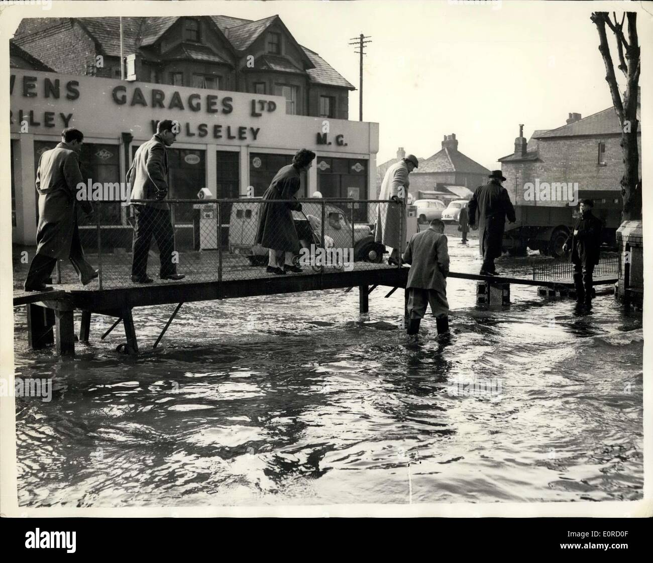 Jan. 24, 1959 - Floods at Maidenhead: Boatmen ferried trapped families to safety today as flood water from the River Thames encircled Maidenhead homes. Emergency calls were answered by many riverside boat builders. Punts, were also used in the rescue work. Photo Shows They had to ''walk the plank'' in Maidenhead High Street today to keep clear of the invading flood waters. Wardens in rubber boots kept watch in case anyone wanted help. - Stock Image